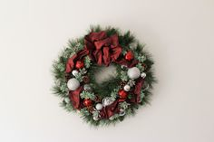 Christmas wreath with red ribbon.  Using silver, clear color ornaments, artificial pomegranates, and artificial succulent.  It measures approx. 22