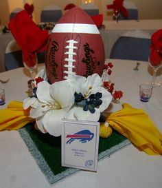 Football themed Wedding Table Centerpiece Idea - Candy filled penalty flags, a square of astro turf painted with yard lines, and a small vase to hold the full sized football.  Remember to keep a sharpie on hand so the footballs can be autographed by the bride and groom.