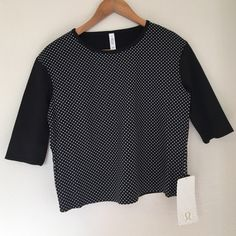Lululemon Tee Lululemon Tee with black and white polka dots, fitted ribbed sleeves, loose fit, hip length, four-way stretch. So cute! lululemon athletica Tops