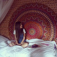 All white bedding with a Persian carpet or Indian tapestry behind the bed.