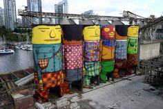 """OSGEMEOS (b. 1974, São Paulo, Brazil), translated as """"The Twins"""", Gustavo and Otavio Pandolfo, have worked together since birth. The street artist duo recently completed their first ever, 360 degree mural on Granville Island for this year's Vancouver Biennale. The ambitious project is a continuation of their ongoing Giants series and is not only their largest public mural to date, but it's the duo's first in Canada."""