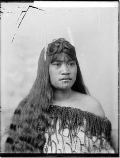 Head and shoulders portrait of an unidentified young Maori woman wearing a korowai (traditional Maori tag cloak). She has a huia tail feather in her hair, and moko on her chin. Some of her long hair is elaborately dressed on top of her head. Photograph taken by William Henry Thomas Partington, ca 1900, probably at Wanganui.