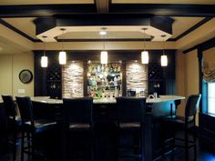 Semicircular Home Bar With Stools  The semicircle shape of this household bar makes for easy conversation, and the high counter helps to conceal the prep area below. Downlights showcase the craggy texture of the stacked-stone walls.