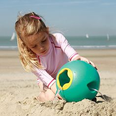 Girl pouring water from a green Quut Ballo beach ball