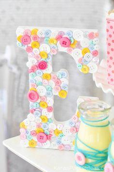 Ideia de decoração para festa no tema Lalaloopsy. Fácilo de fazer: é só aplicar botões de diversas formas e cores na letra inicial do nome da aniversariante.