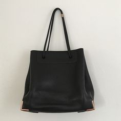 Alexander Wang 'Prisma' Tote Black leather tote with rose gold metal corners on bottom. In used condition with wear on leather. You can see scratches on leather inside on bottom as well as on the bottom of the tote (see pics). There is also wear on metal (see pic). The leather on the body of the tote as well as the handles doesn't show much wear. Pebbles leather so it hold up well. Overall it is in good condition and was recently sent to Alexander Wang for professional cleaning. Please let…