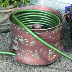 Tame an unruly garden hose inside a decorative metal pot. | Photo: Courtesy of Walmart | thisoldhouse.com