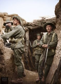 Four exhausted Australian soldiers pose for a candid photograph in the captured Turkish trenches at Lone Pine, Gallipoli Peninsula, on the afternoon of the 6 August 1915. The concealed man at left is drinking from a 'dixie'.