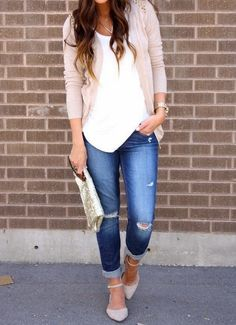 White blouse with light baby pink cute sweater and dark blue stylish casual jeans and cute leather hand bag and light gray cute pumps