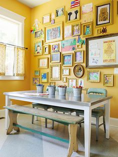 Multiuse Space - A corner of the laundry room is dedicated to a crafts table and a gallery wall of art projects. The homeowner coated most of the frames with the same yellow paint as the walls to unify the space.
