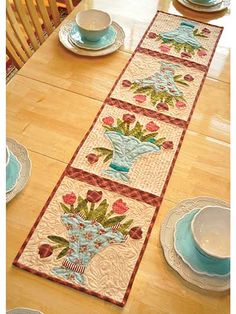 "Decorate your home for spring with this pretty table runner. Use your favorite scraps for the applique, add in tan for the background and finish with a little red plaid for the sashing and binding. Finished size is 12 1/2"" x 53""."
