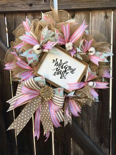 This lovely rustic farmhouse wreath is the perfect piece for your front door! The fun pink color, florals, and wooden script sign makes it such a fun decoration for any farmhouse, rustic, or shabby chic home! This wreath is made on a wire work wreath, natural tan burlap deco mesh, floral ribbon, pink ribbon, white polka dot ribbon, cotton, an oversized bow with a flower made of wood, and a large rustic wooden sign in the center that reads, Welcome yall! This wreath is large measuring at…