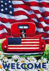 A bright red antique truck with a friendly little black and white pup riding in the bed is the subject of this rustic Americana scene. American flags, green g