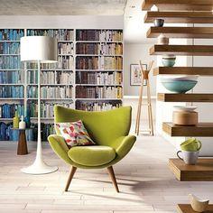 poltrona verde e livros em escala.