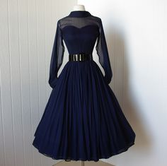 vintage 1950's dress ...beautiful navy silk chiffon full skirt bombshell dress with pintucked nude illusion bodice and billowing sleeves ...a true classic. $170.00, via Etsy.
