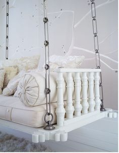 What a great idea.  Refinishing an antique Indian door for the base, adding gorgeous hanging hardware and topping it with a simple but luxe silk cushion and pillows.