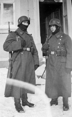 Two Luftwaffe troops on sentry duty wear all the heavy clothing they can muster to keep out the Russian winter. The Germans discovered early on that even the heaviest wool was less of barrier to battle Russian cold. Thus, many German soldiers did not hesitate to strip Russian KIAs of their padded smocks and trousers, not to mention their winter boots, to use them as the necessary alternatives.
