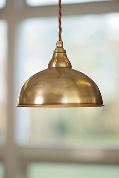 A pendant with a solid brass or steel shade made by jim lawrence
