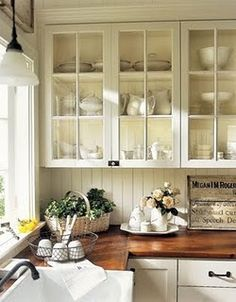 Cream Kitchen cupboards, upper-glass ones, wood counter top, beaded board walls, subway tile backsplash and farmhouse sink.***