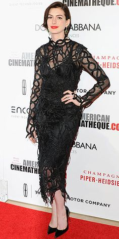 ANNE HATHAWAY Anne goes for a vampy vibe at the American Cinematheque Award gala, pairing her very long-sleeve (the fabric extends to her fingers) lace Christopher Kane dress with Christian Louboutin pumps and a bright red pout.