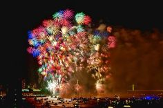 View of Macys Fourth of July fireworks show from Jersey City, New Jersey looking North up the Hudson River with Hoboken on the left and New York City (NYC) on the right. The George Washington Bridge is on the horizon.