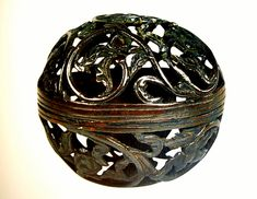 This is a bronze hand warmer from the XII century with stems decorated with stylized plants. It separates into two halves and inside has a small iron vessel where a coal or peat charcoal was placed. Hands were heated but not burned. This type of orbs were used by priests through mass. It's at the Hunt Museum in England.