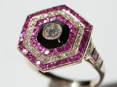 This beautiful Art Deco ring of 18 carat gold is decorated with diamonds and rubies, as well as black enamel. The 29 diamonds (Top Wesselton) have an overall weight of 0.53 carat, the 50 rubies have an overall weight of 1.6 carat. In the middle of the hexagonal ring there is a round-cut diamond which is surrounded by black enamel. A beautiful piece of jewellery in typical Art Deco design!