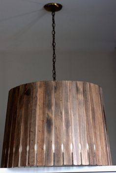 I am so going to do this. It looks like an old wooden bucket turned into a lamp shade, but it's actually wood-stained paint stick mixers hot glued to a lamp shade! I guess you could do the same thing to make a hanging fixture. Wow!