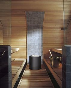 Tulikivi Sumu sauna heater is electric. Here in black. Behind the heater the wall is of soapstone. Tulikivi's media