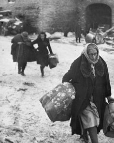 Ardennes Offensive, the Allied Counter Attack 25 December 1944 - 28 January 1945: Belgian civilians carrying personal possessions flee as the Germans opened an artillery barrage against Langlir in an attempt to halt the American drive on Houffalize. Note the old man in the background trying to keep up. The tragedy of the non-combatants.