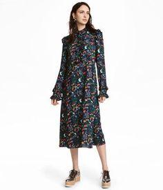 6d56e2e375ad Wadenlanges Kleid aus bedrucktem Webstoff. Das Kleid hat einen schmalen  Volant