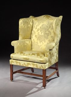 A fine George III Chippendale period mahogany wing chair; of elegant design and fine proportions; standing on square chamfered moulded legs, with a cross stretcher, and castors. The mahogany of lovely colour. Upholstered in yellow silk.
