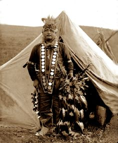 1915 photo shows a young Native American dancer in traditional Lakota dance attire complete with dance bells and feather headdress.