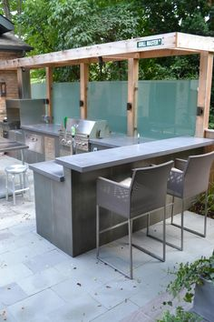 This backyard sanctuary was designed to be a peaceful space for grilling, dining, entertaining, drinking and relaxing. The space features a grill, outdoor refrigerator, concrete counters, a bar area, outdoor furniture, a small cedar pergola, tempered glass panels and a fire pit.