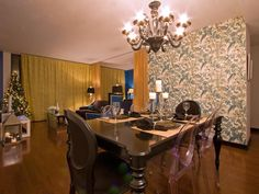 This dining room, with its decorative wall, dark wood table and hardwood floor was designed by Vanessa DeLeon.