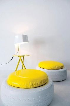 Neumáticos tintados en blanco y convertidos en pufs con decoración de cojín en amarillo. #reciclajeindustrial