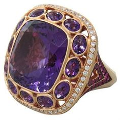 Beautiful modern rose gold ring with large amethyst,surrounded by pink sapphires and diamonds  DESIGNER: Not Signed  MATERIAL: 18K Gold  GEMSTONE: Diamond, Sapphire, Amethyst  RING: STYLE Cocktail Ring  DIMENSIONS: Size - 6.5 Top Of Ring - 28mm x 29mm  WEIGHT: 23g  DIAMOND: WEIGHT 0.62ctw  GEMSTONE(S): DIMENSIONS Amethyst - 22ct ,Pink Sapphires - 0.79ctw  CONDITION: Estate  PRODUCT ID: 12468