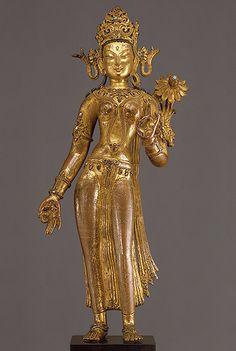Estatua de Tara de pie- siglo 14- Nepal. Tara, la salvadora es la diosa más importante en el panteón budista. Representada aquí en pie, con su mano derecha en un gesto de bendición llamado varadamudra y con su mano izquierdo realizando un gesto ritual denominado vitarkamudra. Se le ha representado con un cuerpo voluptuoso vestida con una túnica abierta con adornos florales, la estatua esta ricamente adornada de joyas incluyendo una corona, pendientes, collares y brazaletes...