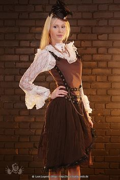 A lovely steampunk style pleated skirt dress with great eyelet detail down the side and at the waist with golden chain attached. The shoulder straps are adjustable with eyelets and buckles. The dress has a stunning pleated chiffon draped overlay from the waist and has lace and bow trimming.