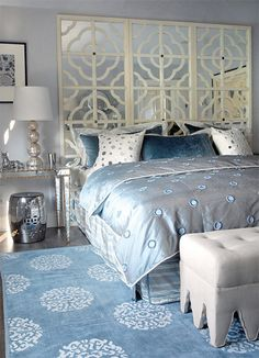 Glam bedroom with gray blue walls paint color, mirrored console table nightstands with gold trim, ivory mirrored quatrefoil pattern floor screen used as headboard, champagne metal lamps, silver garden stools, Madeline Weinrib Atelier Light Blue Mandala Rug and light gray linen tufted ottomans.