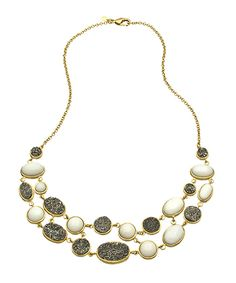 It's always a happy occasion when pulling this Andara silver druzy pebbles necklace from your jewelry box. Shimmering oval druzy trinkets in various sizes, are complemented by pearly white agate pebbles. This is a wonderful statement piece for decorating your neckline no matter which outfit you're wearing.    Stone: Druzy, agate  Metal: Gold plated  Chain length: 18 inches  Bib length: 7 inches  Bib width: 1 inch      Style #MC0812AN06