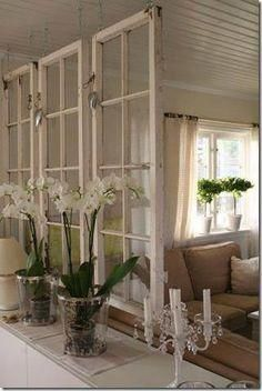 Windows hung as a room divider. The fresh flowers makes it feel like you are outdoors.