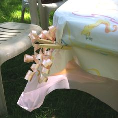 Great tip to keep your tablecloths on at that windy outdoor party. Curling ribbon on clothespins, place on all four corners, voila stays in place:)