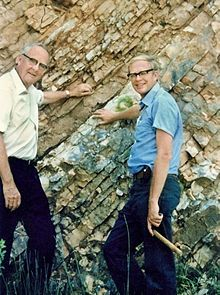 1979: From excess traces of iridium in late Cretaceous rocks, American scientist Luis Walter Alvarez theorizes that a large comet or asteroid struck the earth 65 million years ago, raising clouds of dust that reduced the amount of solar radiation penetrating the atmosphere and triggering the mass extinctions of dinosaurs and other Mesozoic life. Luis and Walter Alvarez at the K-T Boundary in Gubbio, Italy, 1981.
