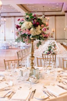 wedding reception centerpiece of white hydrangea, lavender roses, purple stock, lavender lisianthus, light pink stock, burgundy scabiosa, pink wax flower, queen anne's lace, lavender crepe myrtle blooms and silver dollar eucalyptus on a tall gold pedestal.