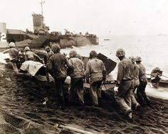 80-G-304855: Battle for Iwo Jima, February-March 1945. Navy Medical Corpsmen of the Fourth Marine Division arrive at the beach on Iwo Jima with their wounded after a long hazardous trip from the front lines. Three men carrying a stretcher case lead the way to the evacuation boat while others help the walking wounded. Photographed released, February 26 1945. U.S. Navy Photograph now in the collections of the National Archives.