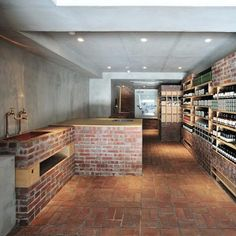 Brick courses infill the spaces between wooden shelves where products are displayed, while brick units with wooden surfaces house sinks.