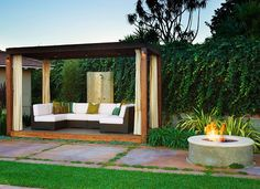 modern simple exterior pergola covered sectional outdoor seating with concrete round firepit