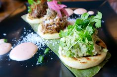 A trio of arepas-- shredded skirt steak, shredded chicken and pulled pork, topped with avocados, cilantro and pickled onions. SO GOOD! Many Latin inspired dishes at