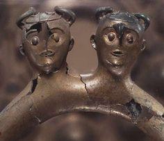 Viksø-hjelmenes opbygning. Viksø-hjelmenes brug af horn og krogformede næb i panden ses også på disse to menneskefigurer, der pryder en mankestol fra Fogdarp i Skåne. Yngre bronzealder.